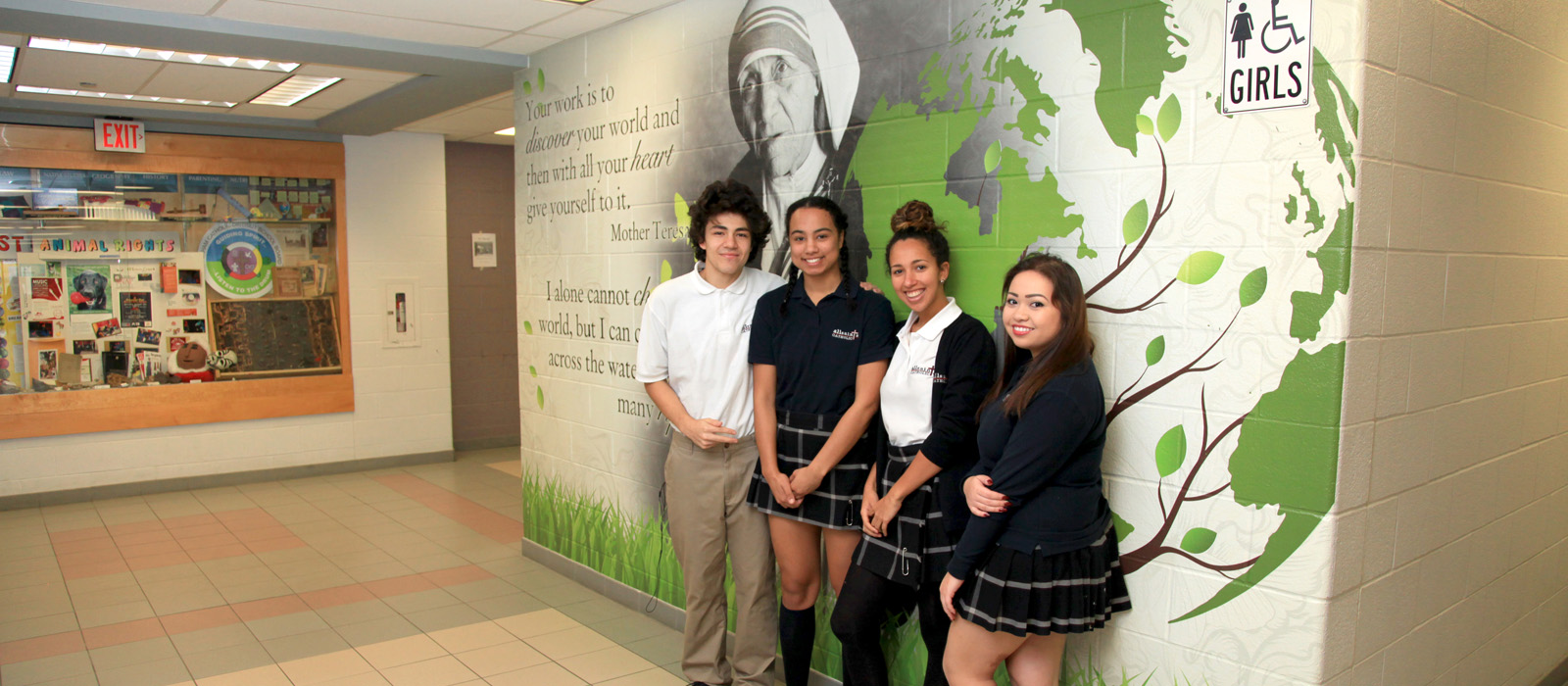 four students standing in front of a mural depicting a quote and picture of Mother Teresa.