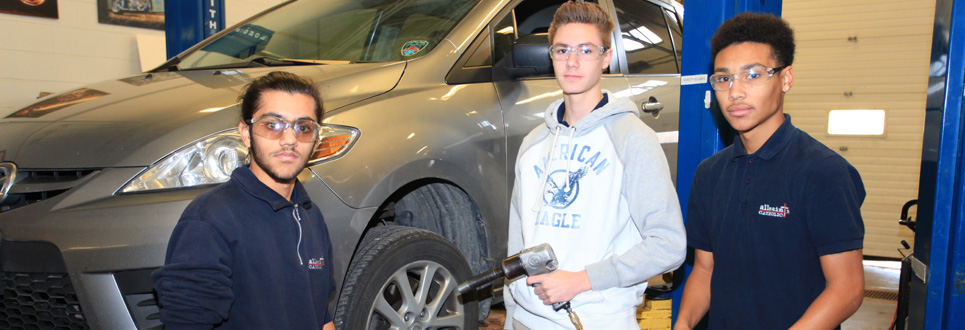 Three male students in an auto shop classroom with car behind