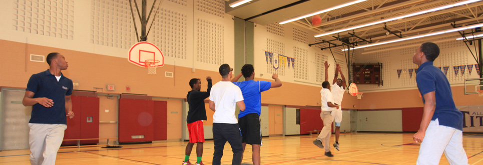 Several students playing basketball in a gym.